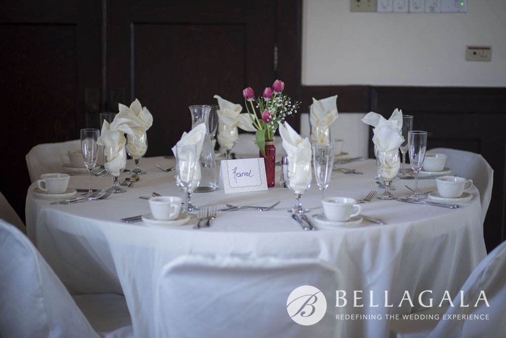 round table setting with white linens, chair covers and white cups/saucers with red tulips centerpiece
